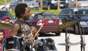 Noah Pierre vocalizing and banging on drums at the Spring Lunch Jam.
