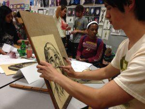 Senior Luke Ferguson draws another student's portrait while Junior Jewel Stevenson looks on in awe.