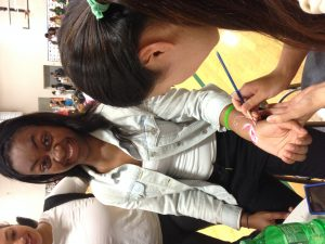 Junior Heather Sun paints flower on Sophomore Elicia Craig