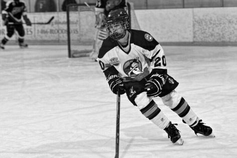 Ryan Allison skates to the puck during his ice hockey game (Photograph courtesy of Ryan Allison).