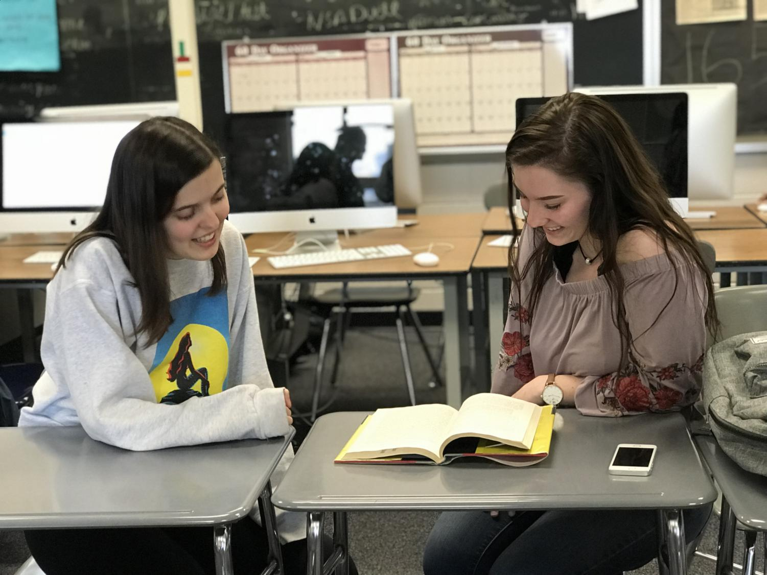 Jane Hilger and Savannah Jackson discuss a book during some free time.