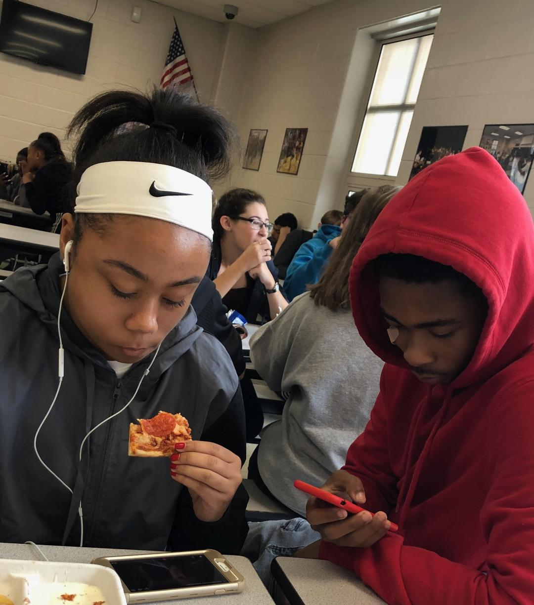Macayla Miles (junior) and Corey Cooke (senior) enjoy their free lunch period preoccupied with their cellphones.