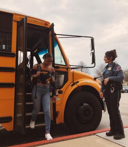 Senior Darae Lyles gets off of her bus to be greeted by Officer Shams