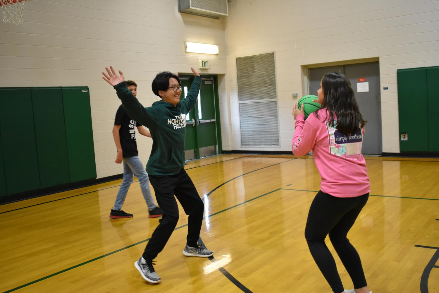 Freshman Matthew Batmukh and Nakomis Styers, are seen playing basketball in the Aux Gym.