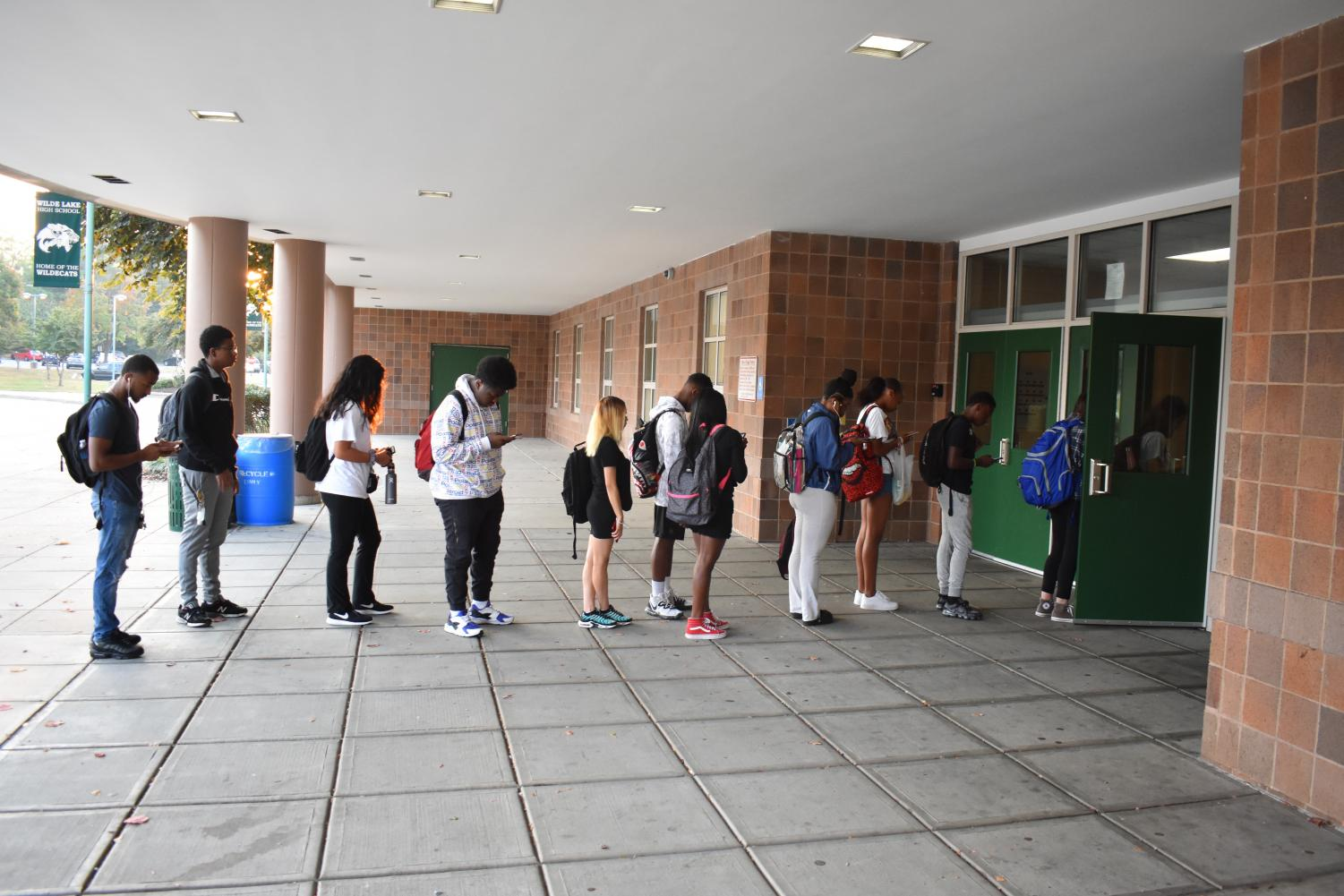 Numerous students are seen lined up outside of the main entrance awaiting a tardy pass.