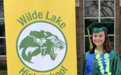 Laura Krell, Wilde Lake senior, takes a picture in her cap and gown at school.