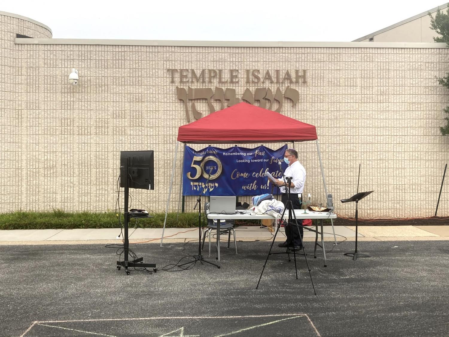 Rabbi Axler leading services in the parking lot in front of Temple Isaiah.