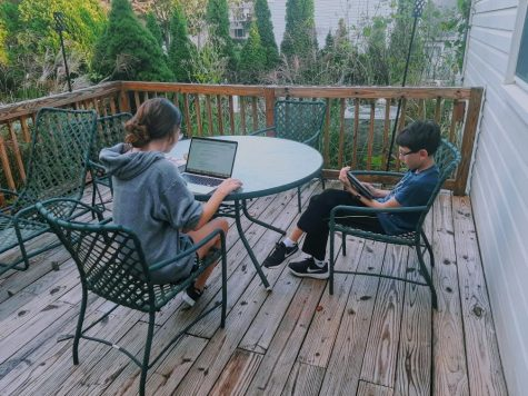 Sarah Rubin and her brother, Daniel, do homework outside together.