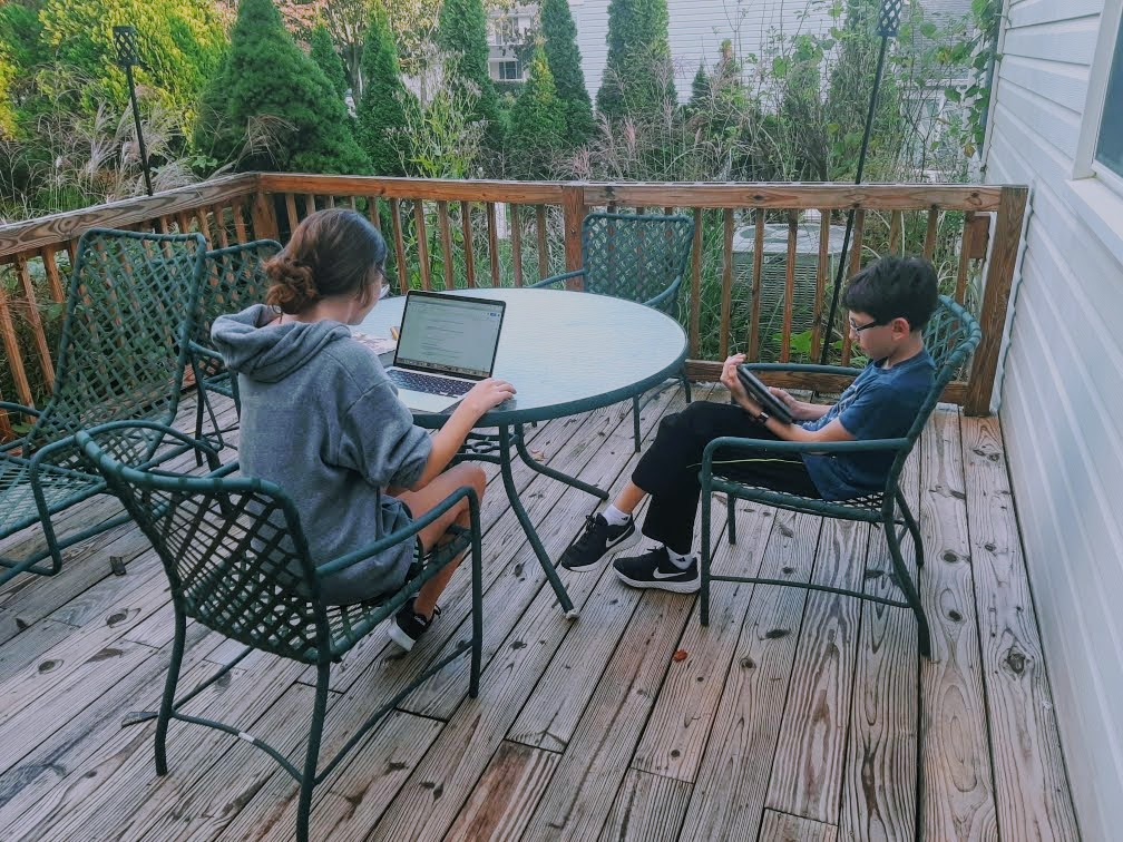 Sarah and her brother, Daniel, do homework outside together.