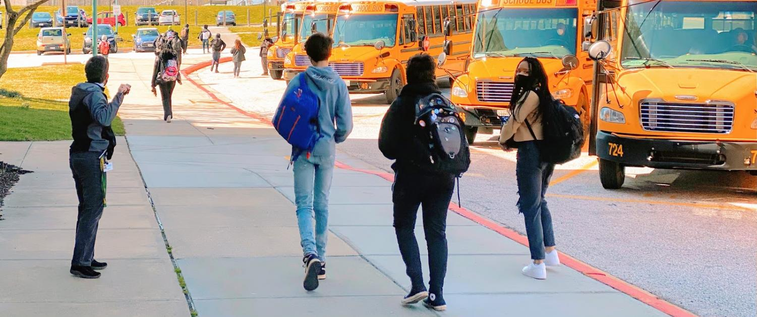 A group of students walking away from the school after dismissal at 2:30. Principal Leonard (on the left) says goodbye to the departing students while simultaneously coordinating bus drivers and staff.